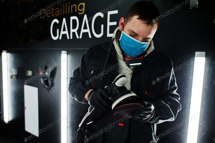 Car detailing concept. Man in face mask with orbital polisher in repair shop garage.