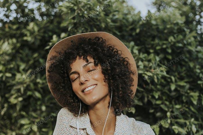 Schöne Frau Musik hören in einem botanischen Garten