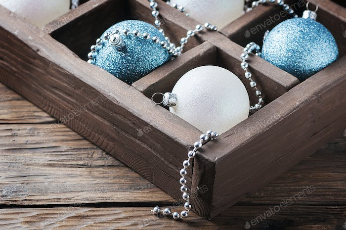 Box with christmas balls on the wooden table