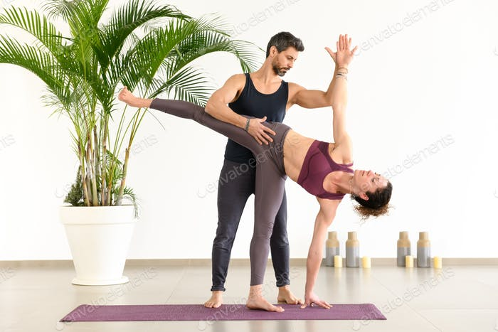 Trainer assisting a woman doing a half moon pose