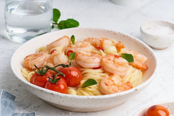 Seafood pasta spaghetti with fried shrimps, bechamel sauce, mint leaf and tomatoes on white table