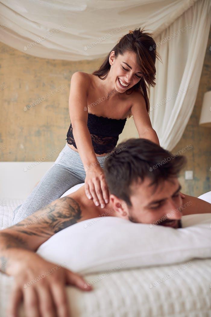 Pareja relajándose en el dormitorio. Pareja feliz haciendo masajes.