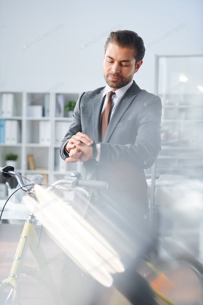 Young elegant businessman looking at wristwatch in office