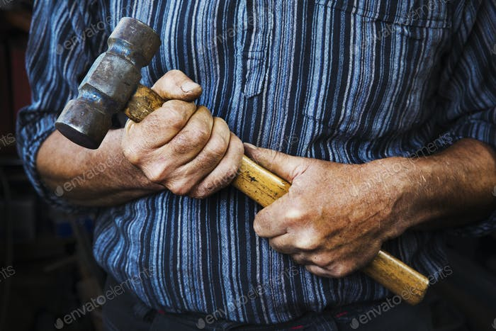 Close up of blacksmith's hands gripping a large hammer.