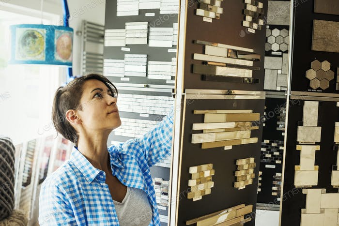Woman looking at merchandise in an interior design store. Fixtures and fittings, tile samples,