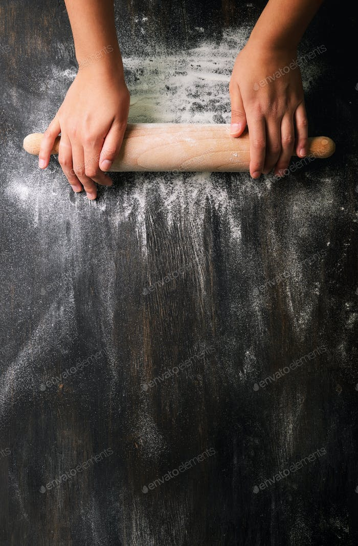 Girl hands keep rolling pin with flour on dark black table, baking background, top view, copy space