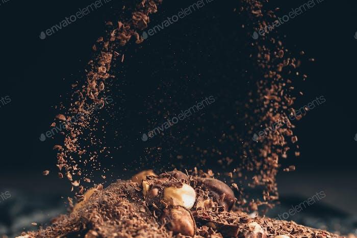 Fallende zerkleinerte Schokoladenstücke auf einen Schokoladenhaufen