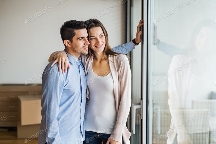 Young couple moving in a new home, looking out of a window.