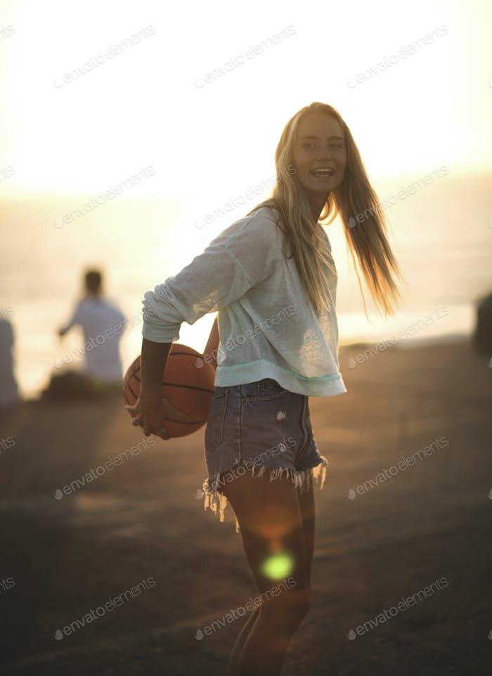 Junge Frau, die vor einem Sonnenuntergang steht, hält einen Basketball.
