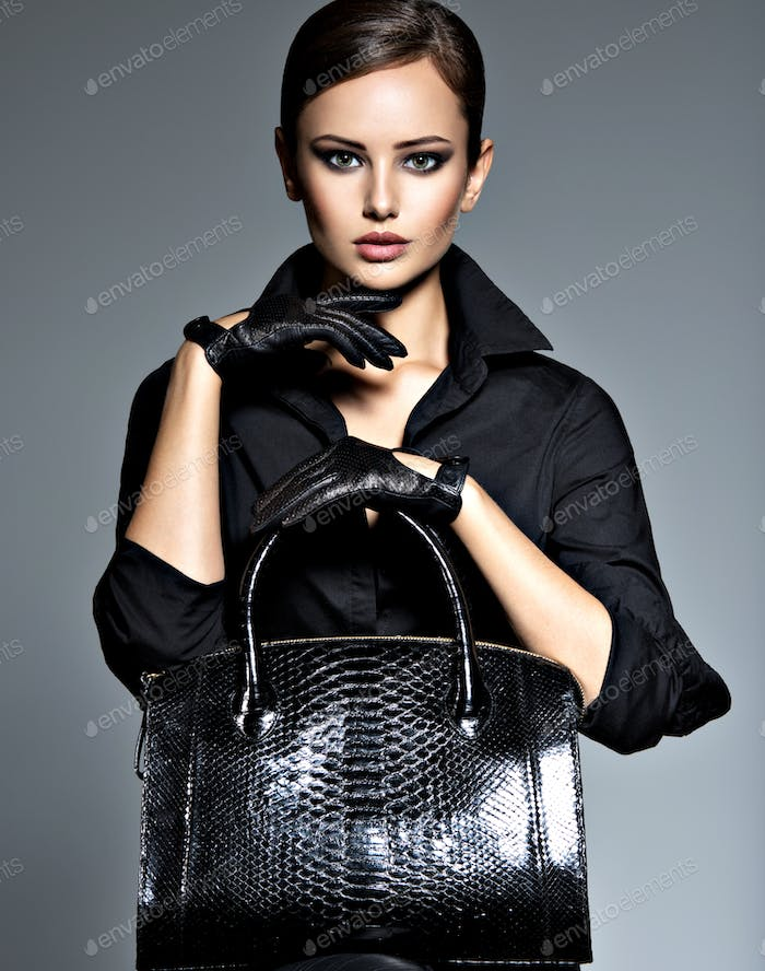 Beautiful woman in black  holds fashion handbag
