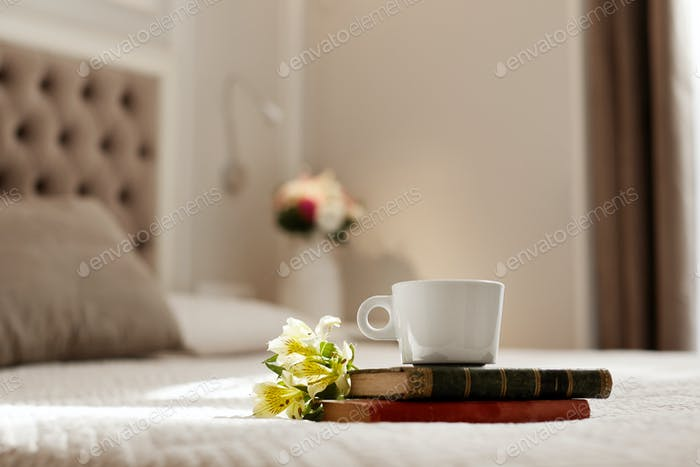 Books, flowers, and a coffee Cup lie on the bed. Romantic gift, coffee in bed