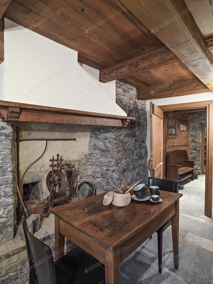 Interiors of a Rustic Kitchen with Fireplace and Old Furniture