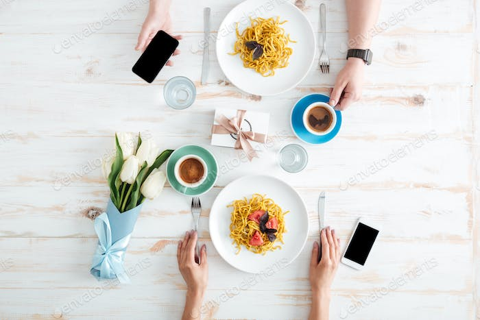 Hands of young couple eating pasta on wooden table
