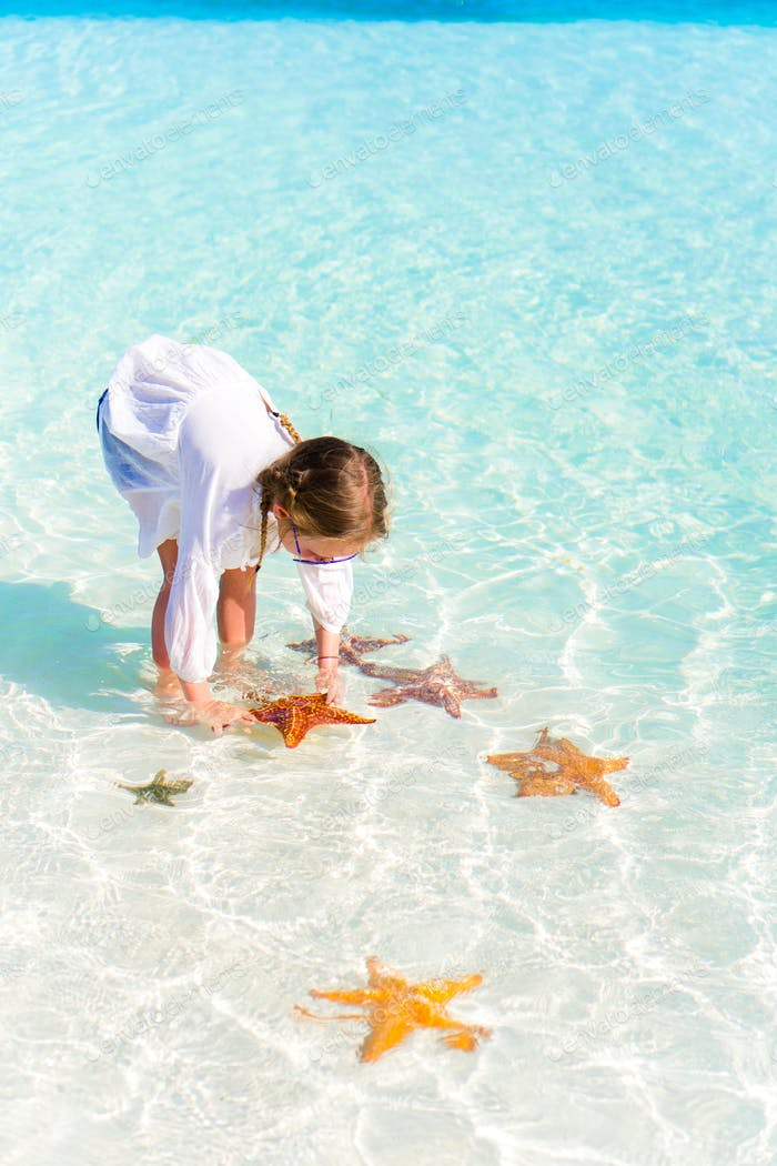Adorable little girl with starfishes in water at clear water