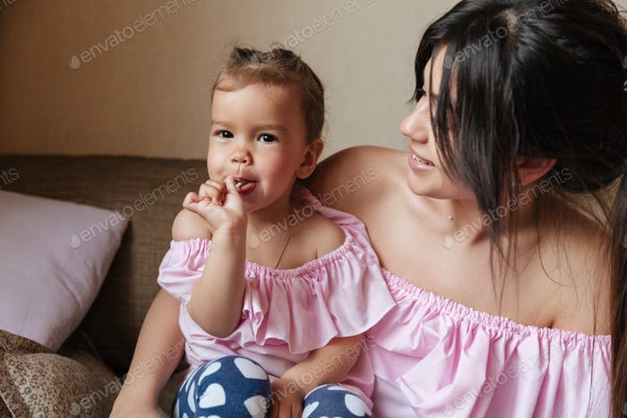 Happy young mother sitting on sofa with daughter eating candy