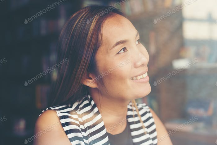Cheerful woman sitting and thinking looking away to the sky.