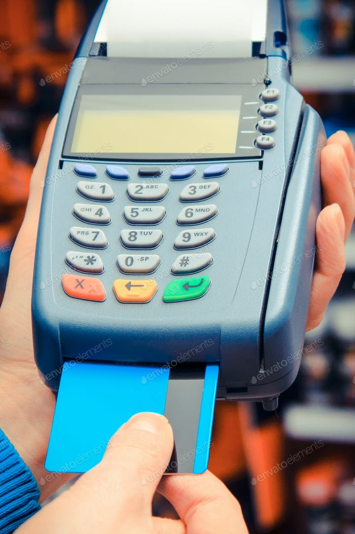 Using payment terminal and credit card in shop, cashless paying for shopping or products concept