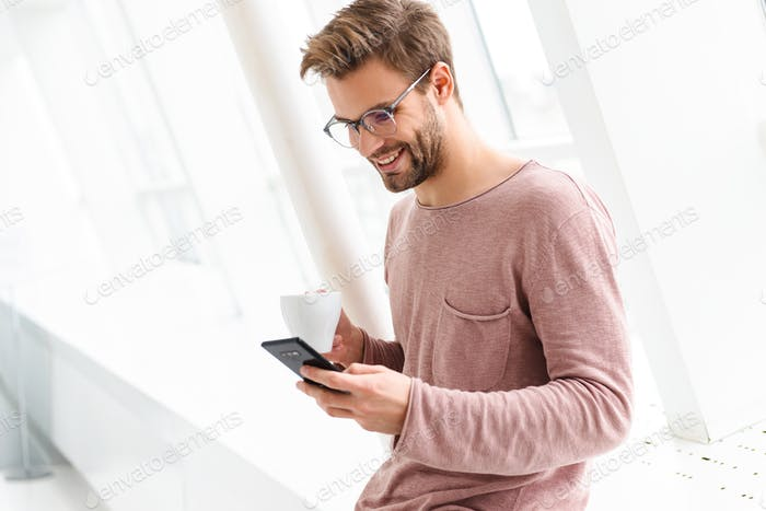 Image of man holding smartphone while standing over window indoors