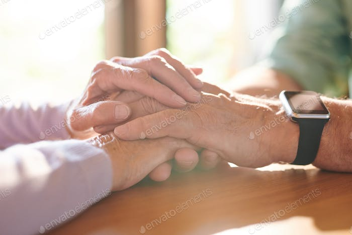 Pile of hands of contemporary supportive senior husband and wife