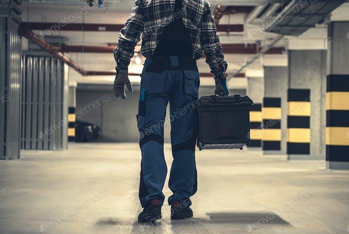 Trabajador técnico con caja de herramientas grande en las manos