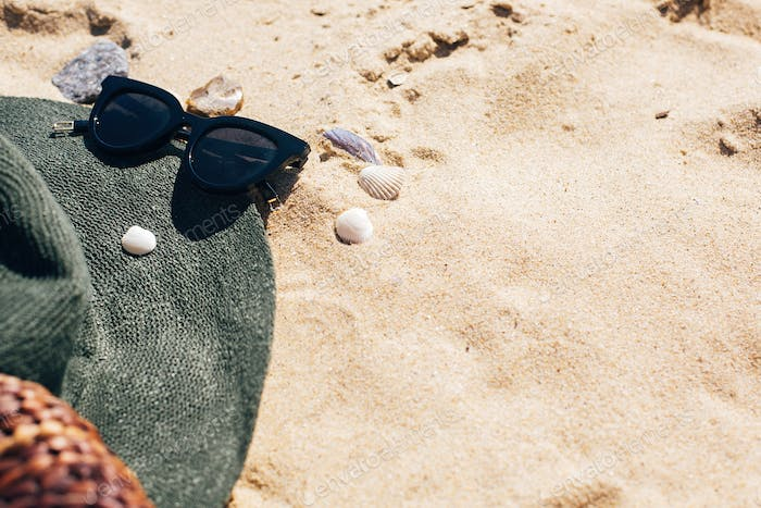 Stylish hat, sunglasses and slippers on sandy beach