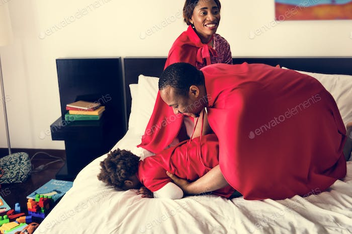 Black family playing together on bed