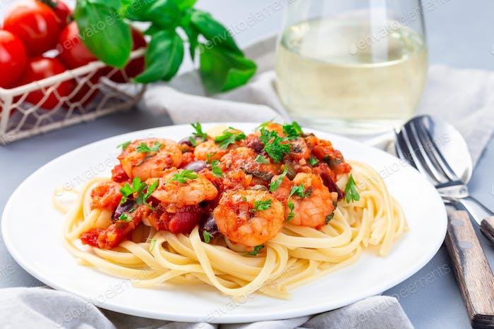 Italienische Linguine Puttanesca, Pasta mit Garnelen in Tomaten-Basilikum-Sauce horizontal
