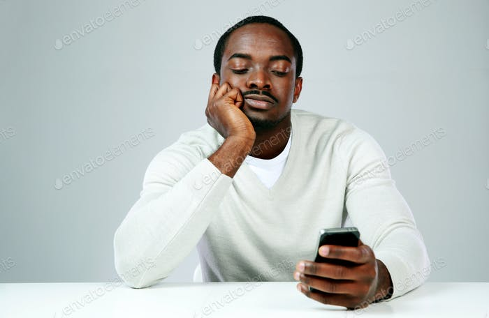 Pensive african man using smartphone on gray background
