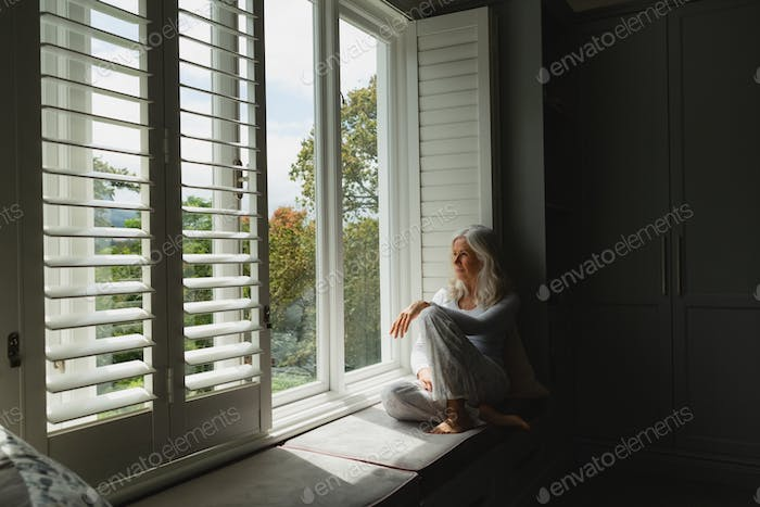 Side view of thoughtful active senior Caucasian woman looking through window at home