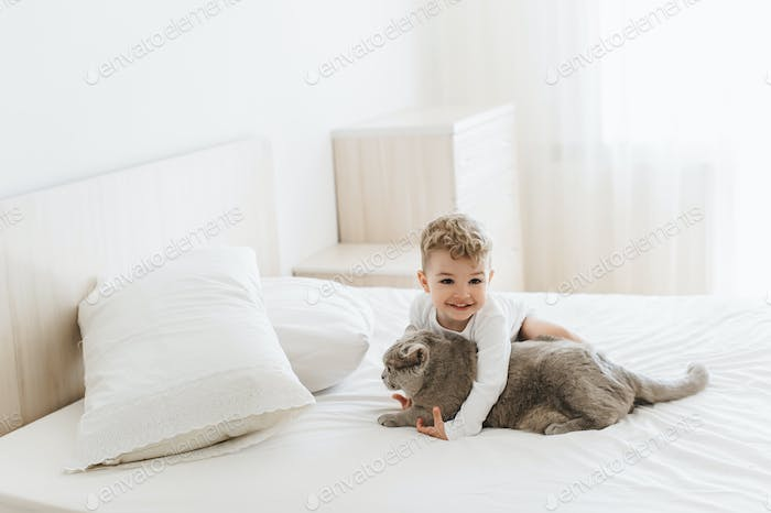adorable smiling child playing with grey british shorthair on bed at home
