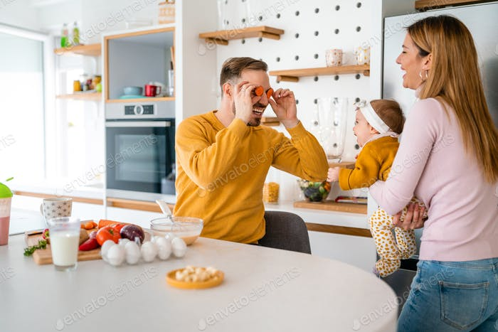 Happy family preparing healthy food together in kitchen