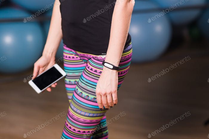 Thumbnail for Close-up of female hands with fitness tracker and smartphone in gym