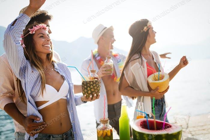 Grupo de Amigos divirtiéndose y bailando en la Playa. Fiesta de verano en la Playa