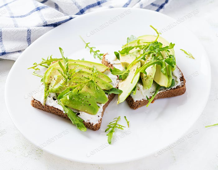Sandwich of cream cheese bread and slices of avocado on a plate