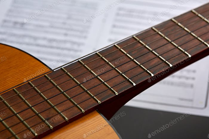 Acoustic guitar, music book on background, nobody