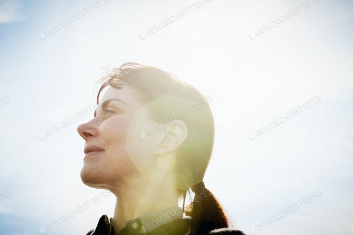 A woman, low angle view, side profile, looking upwards. Lens flare.