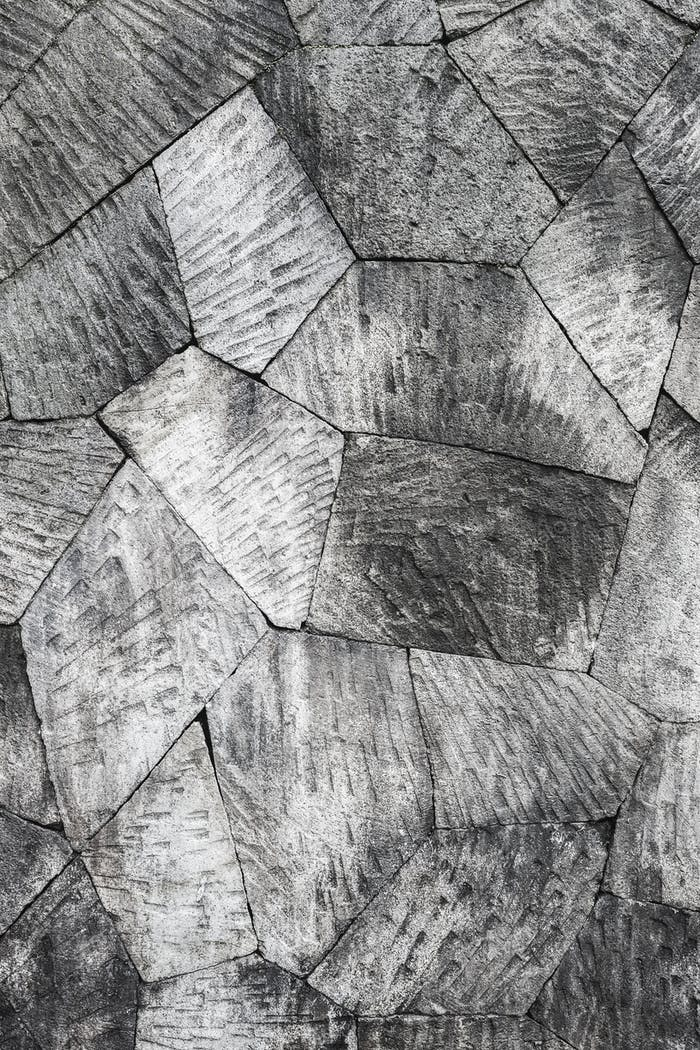 Grey stone wall background, pattern with different geometric shapes.
