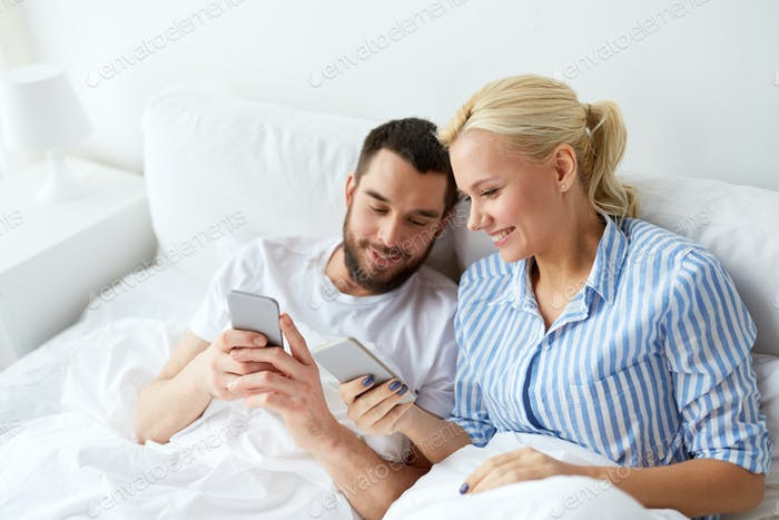 happy couple with smartphones in bed at home