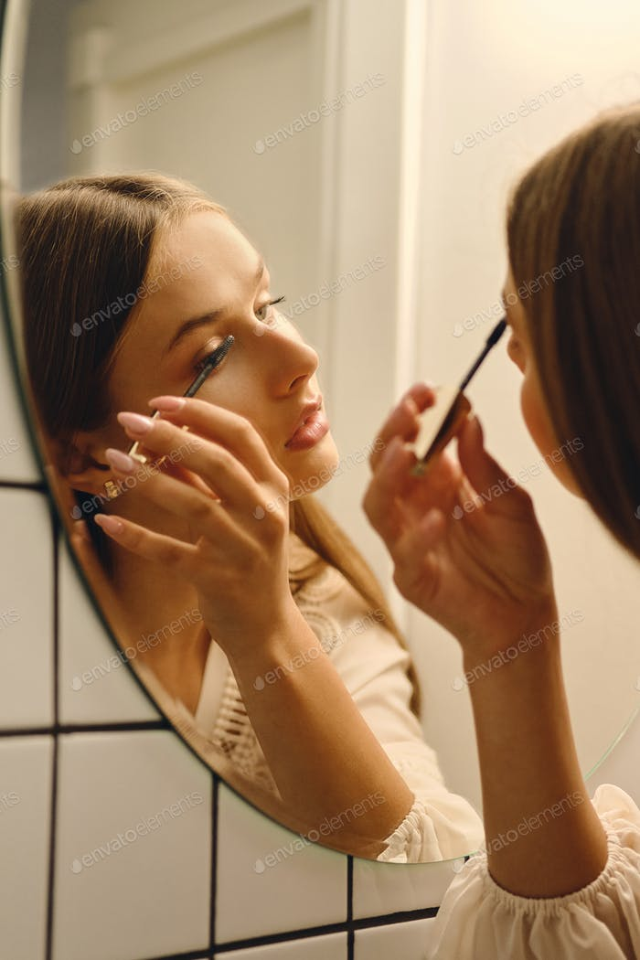 Young attractive woman in white dress dreamily applying black mascara in front of mirror in bathroom