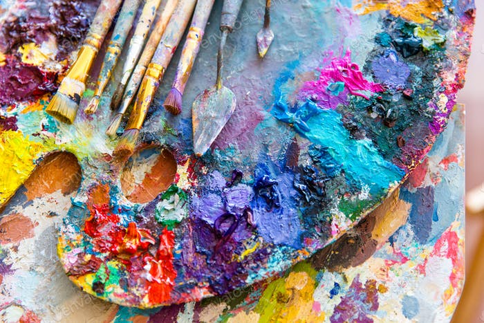Closeup of art palette with colorful mixed paints and paintbrushed