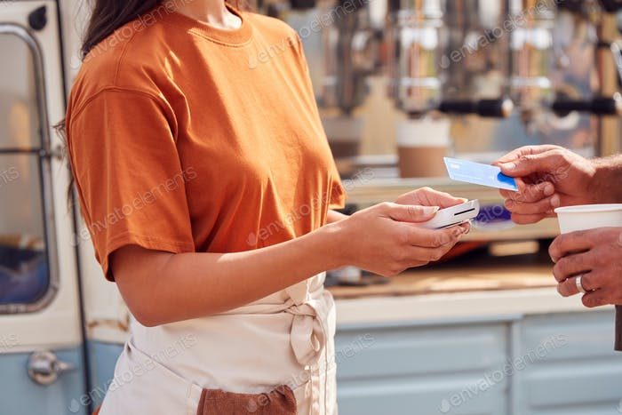 Close Up Of Customer Making Contactless Payment At Mobile Coffee Van