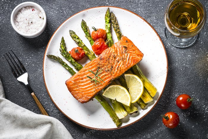 Baked salmon fish fillet with asparagus and tomato top view.