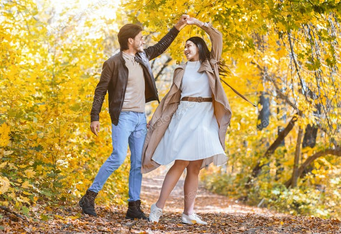 Romantic joyful couple dancing in the middle of forest