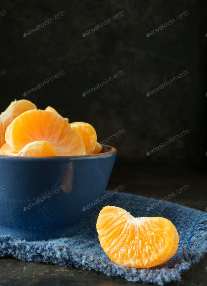 A blue bowl of orange tangerine segments
