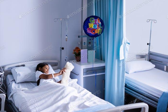 Patient entspannt auf dem Bett mit Teddybär