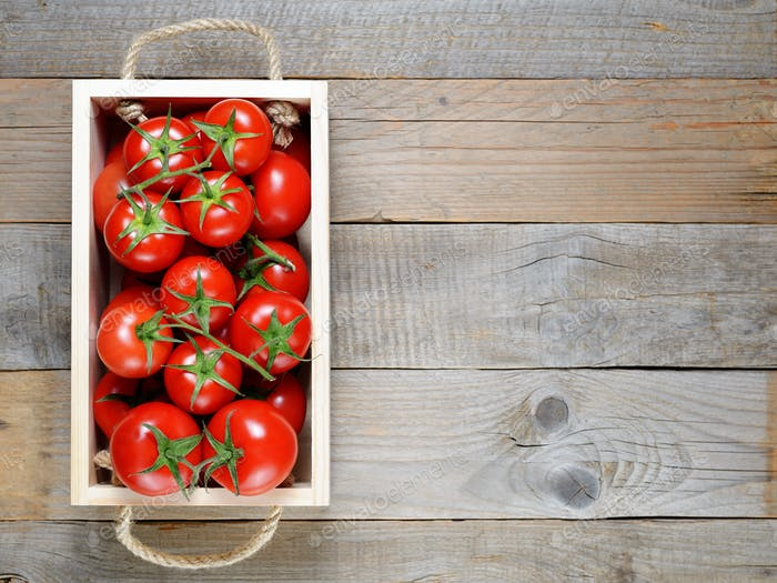 Tomatoes in wooden box on table top view
