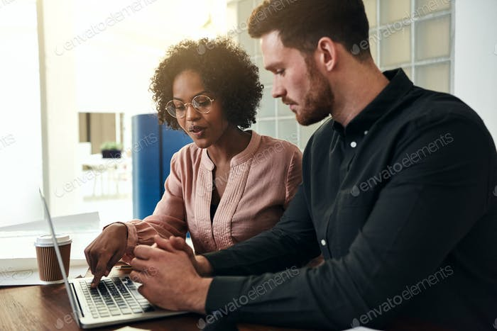 Two diverse colleagues using a laptop in a modern office