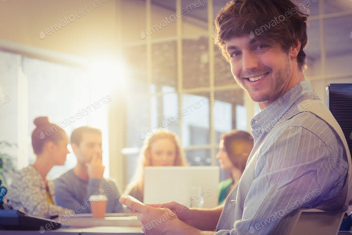 Portrait of smiling young businessman with colleagues in the office