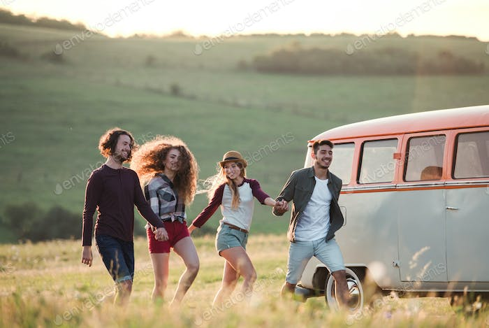 A group of young friends on a roadtrip through countryside, running.