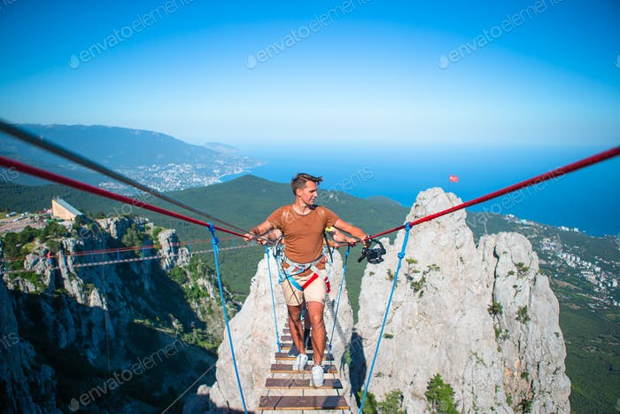Man crossing the chasm on the rope bridge